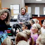 Henely looks at a package in front of several kindergarteners. In the backround, Mrs. Christianson holds a carrier with Mrs. Henely's newborn.