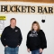 "Brian and Heather stand side-by-side, both wearing jeans and black jackets. Above them is a sign reading, ""BUCKETS BAR."""