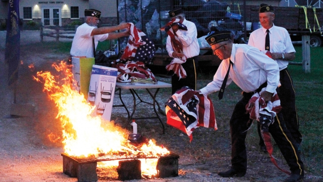 Alvin places a US flag on the fire as other American Legion members, all in uniform, handle and prepare more flags for disposal.