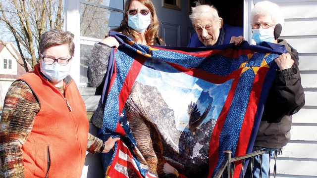 Susan, Karen, and Linda stand around Alvin, holding up a red and blue quilt depicting an eagle.