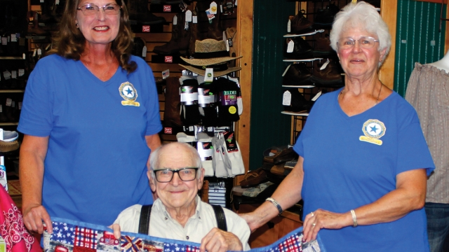 Karen and Linda wear matching blue Auxiliary t-shirts and stand behind LeRoy Weaver, sitting, who holds a red, white, and blue quilt.