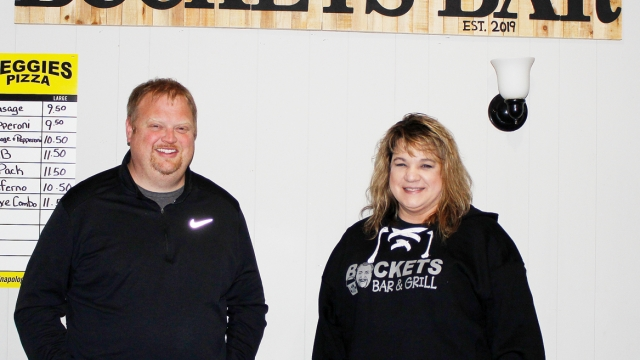 """Brian and Heather stand side-by-side, both wearing jeans and black jackets. Above them is a sign reading, """"BUCKETS BAR."""""""