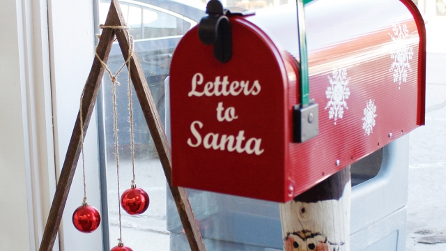 """A red mailbox with green flag and snowflakes on the side reads """"Letters to Santa"""" on the front. Beside it is a wooden Christmas tree, and behind is a window looking out onto the street."""