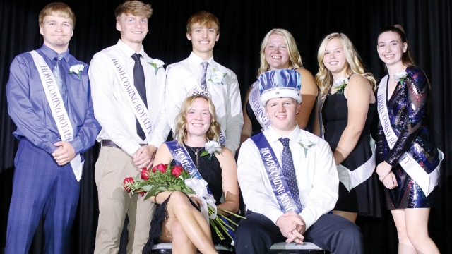 """The homecoming court stands behind Emma and Thomas, who are seated and wearing a tiara and crown, respectively. All wear sashes saying """"Homecoming Royalty,"""" with Emma and Thomas' denoting queen and king. Emma also holds a bouquet of roses."""