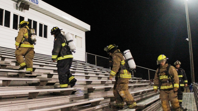 Five firefighters in full gear climb the bleachers at Bison Field.
