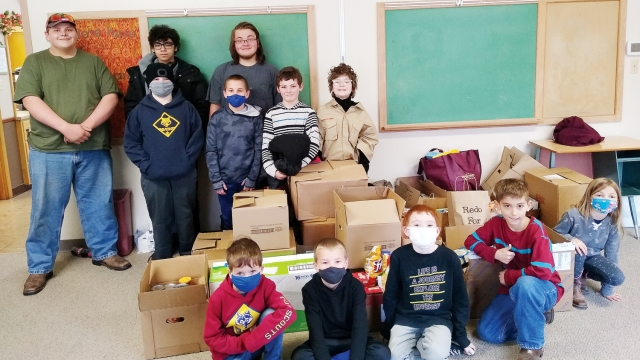 Several children and teens stand and sit around boxes of food, most wearing masks.