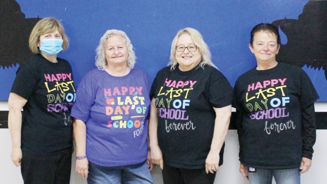 """The four retirees stand side-by-side, all wearing t-shirts that say """"Happy Last Day of School Forever."""""""