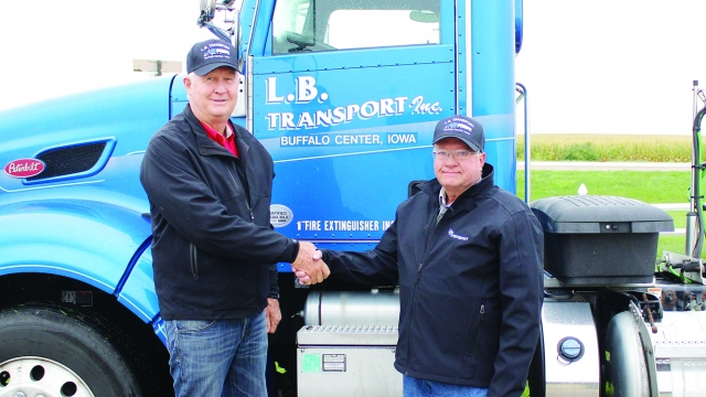 Terry and Dale stand, shaking hands, in front of a blue semi truck.