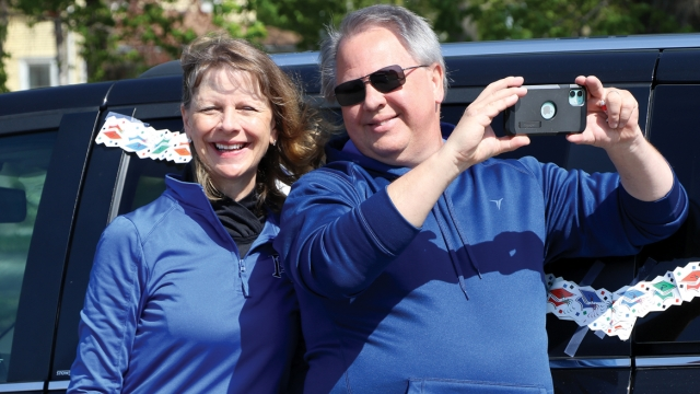 Mrs. DeBoer and her husband stand in front of a vehicle, Doug holding a phone to record a parade.