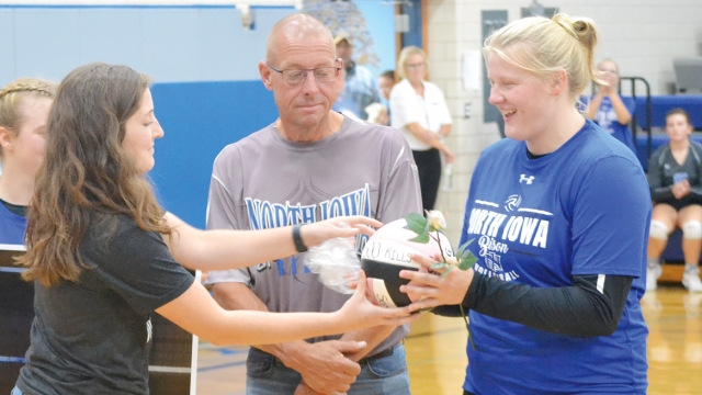 """Coach Micah presents Leah with a volleyball and white rose. Written on the volleyball is """"500 Kills""""."""