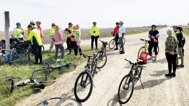 Bicyclists gather at a split at the road.