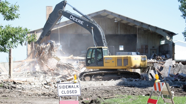 An excavator tears down the old Rake building. Part of the building still stands behind it, while a sidewalk closed sign sits infront of the demolition zone.