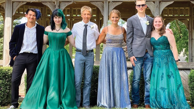 Izzy Salas, Hope Henton, Gunner Mathahs, Hannah Boekelman, Jack Langfritz, and Kali Bengtson stand in a row. Hope, Hannah, and Kali all wear teal or blue full-length dresses, while Izzy, Gunner, and Jack wear suits ranging in levels of formality.