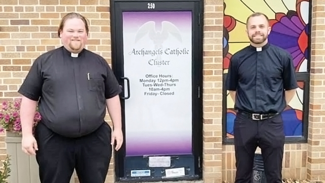 Fathers Andrew Marr and Joseph Sevcik stand on either side of a sidewalk, a door and stained glass window behind them.
