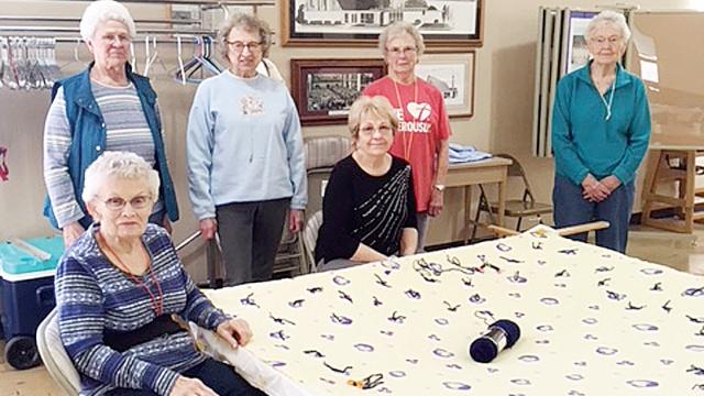 Six elderly women gather around a quilting frame.