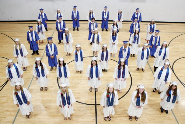 The class of 2020 in blue and white regalia stands spaced apart in the North Iowa gymnasium.
