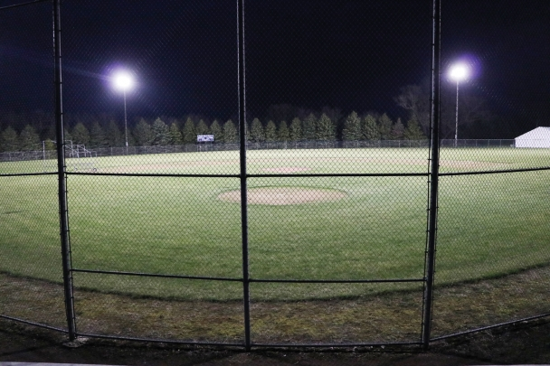 The baseball diamond at North Iowa is lit up at night with the overhead lights.