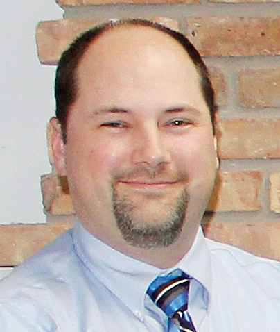 Joe Erickson smiles, wearing a blue shirt and tie.