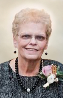Judy smiles, wearing wire-rimmed glasses and a flower corsage.