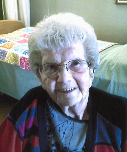 Lillian Halverson smiles, wearing a color-block sweater in black, blue, red, and magenta, and a gray blouse with flower on it. Behind her is a care center room with a quilt on the bed.