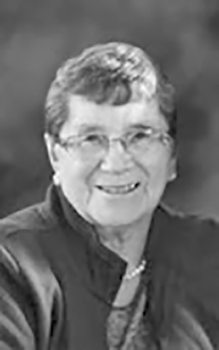 A black and white photo of Phyllis, who is smiling widely.