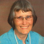 A professional portrait of Joan. She wears a blue button-up, glasses and pearl necklace.