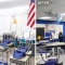 A before and after set of photos of an elementary classroom. On the left (before) the classroom has white walls, drop lights and indiviudal desks. On the right is the same classroom with one blue wall, a drop ceiling, new desks that interconnect, and windows which have the lower half blocked out.
