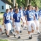 Football players step onto a road, wearing blue jerseys with white numbers and pants.