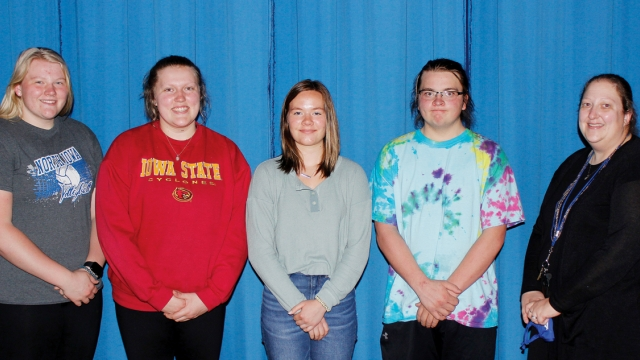 Four students stand in a line beside advisor Amanda Heyer.
