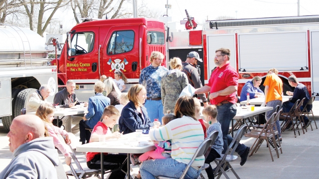 A group of people sit at tables outside with a firetruck in the background.