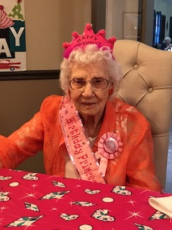 Bertha sits at a table with a pink table cloth. She wears a pink crown, ribbon, and sash all referencing her birthday.