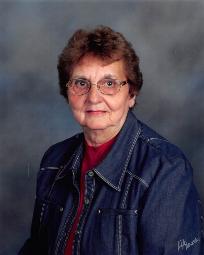 Deloris sits in front of a blue-gray background, wearing a red blouse, denim jacket, and glasses.