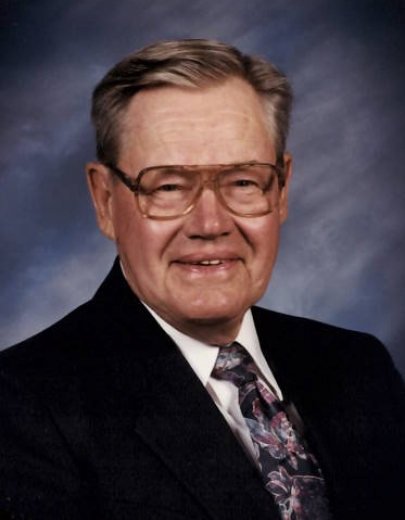 Andre Torkelson smiles in front of a blue background. He is wearing a suit and tie and wire-rimmed glasses.