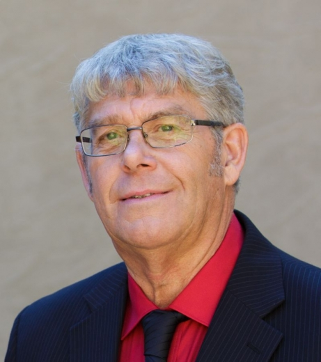 Jeffery Blome smiles at the camera, wearing a suit, tie, and glasses.