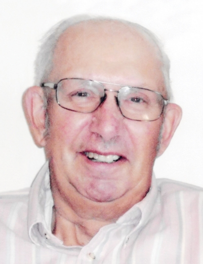 Larry smiles in a close-up photo. He wears large, wire-framed glasses and a button down shirt.