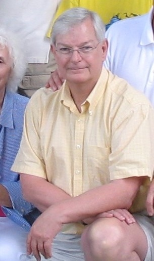 A photo of Ray kneeling, cropped from a group photo. He wears glasses and a pastel yellow polo shirt.
