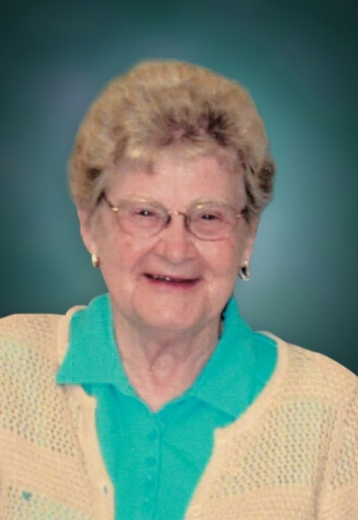 Shirley smiles with her mouth open. She wears a teal blouse with a light orange cardigan.