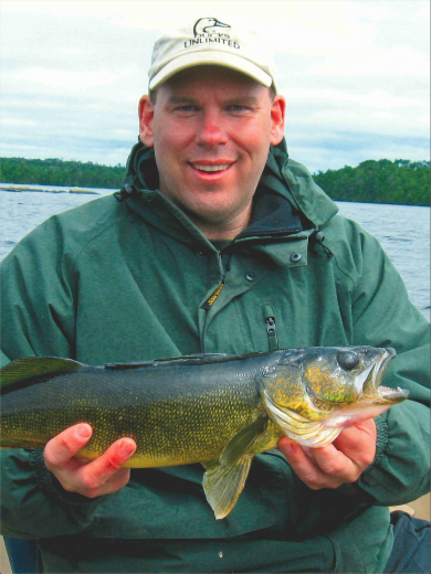 Paul smiles, holding a large fish.
